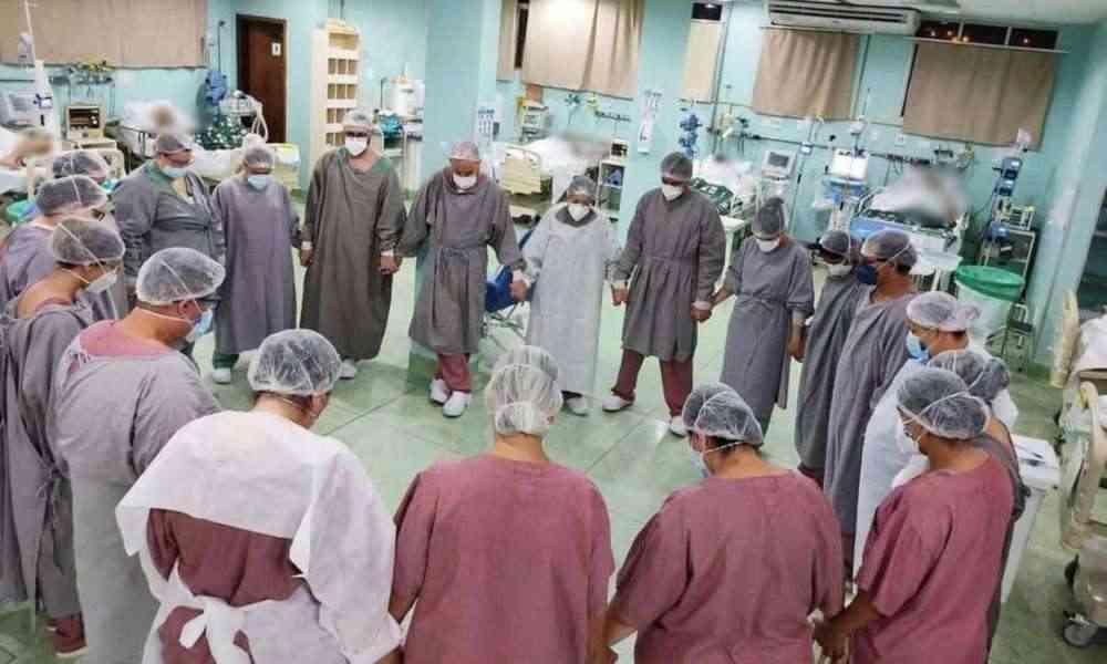 Médicos y enfermeras oran por pacientes hospitalizados con COVID-19