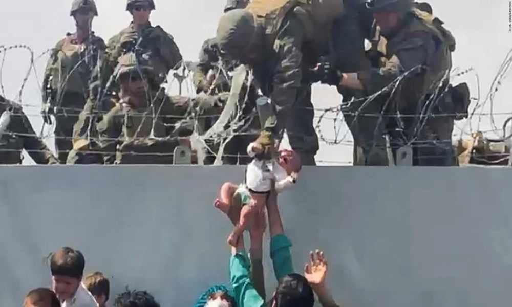 Afgano le entrega su bebé a un soldado estadounidense por encima de un muro